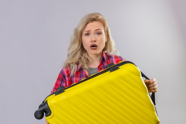 Jovem viajante triste vestindo uma camisa vermelha segurando uma mala na parede branca isolada