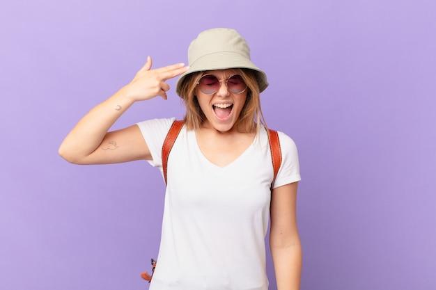 Jovem viajante turista olhando infeliz e estressada gesto de suicídio fazendo sinal de arma
