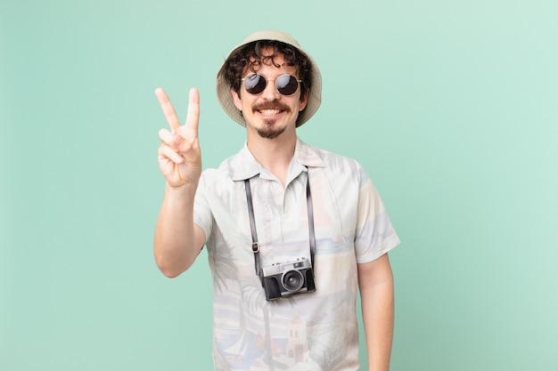 Jovem viajante turista sorrindo e parecendo amigável, mostrando o número dois