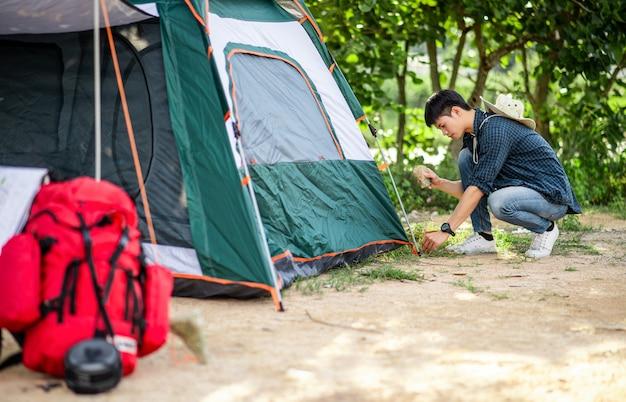 Jovem viajante usa uma pedra para bater nas estacas da barraca na floresta durante um acampamento nas férias de verão