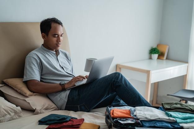 Jovem viajante usando laptop com mala cheia de roupas