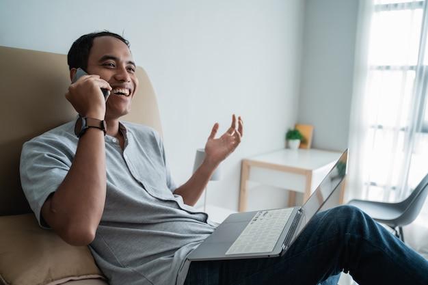 Jovem viajante usando laptop e falando por telefone