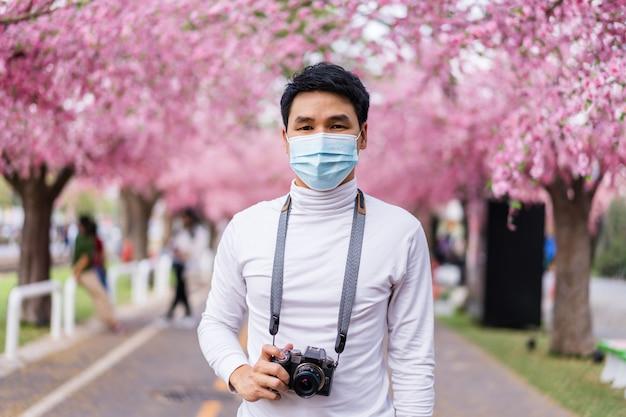 Jovem viajante usando máscara facial e olhando flores de cerejeira ou flor de sakura florescendo no parque
