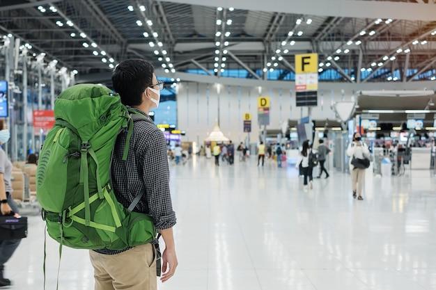 Jovem viajante usando máscara médica e verificando o tempo do voo no terminal do aeroporto