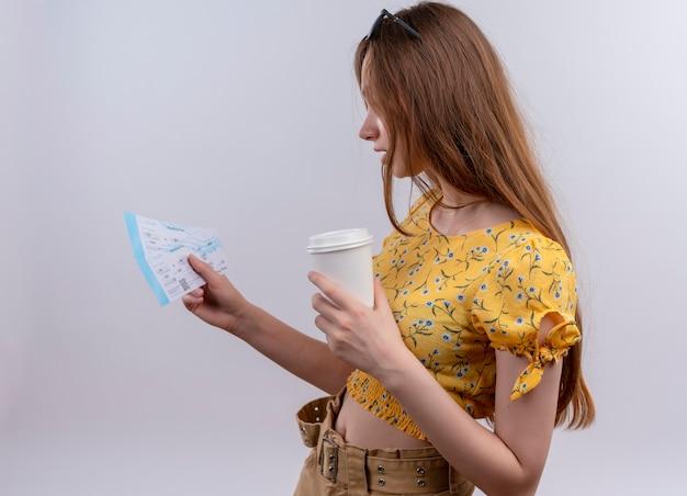 Jovem viajante usando óculos escuros na cabeça, segurando as passagens de avião e uma xícara de café de plástico e olhando para as passagens em vista de perfil na parede branca isolada