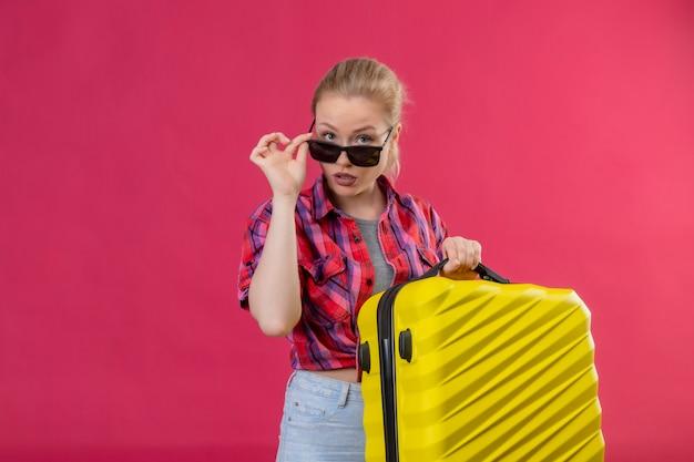 Jovem viajante vestindo camisa vermelha de óculos segurando uma mala na parede rosa isolada