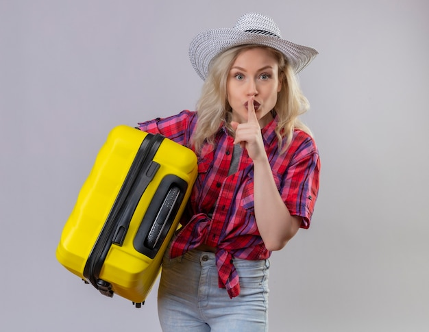 Jovem viajante vestindo camisa vermelha e chapéu segurando uma mala, mostrando gesto de silêncio em parede branca isolada