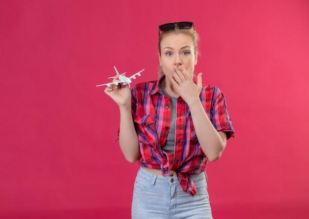 Jovem viajante vestindo camisa vermelha e óculos na cabeça, segurando o brinquedo plano coberto com a boca na parede rosa isolada