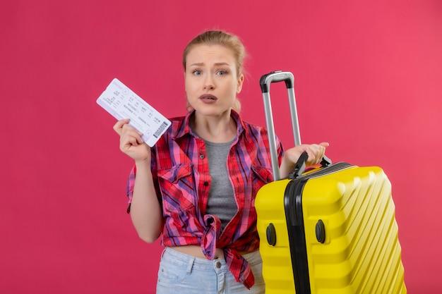 Jovem viajante vestindo camisa vermelha segurando mala e passagem na parede rosa isolada