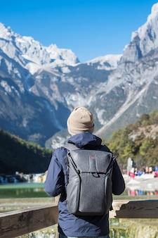 Jovem viajante viajando no vale da lua azul, marco e local popular dentro da área cênica de jade dragon snow mountain, perto da cidade velha de lijiang. lijiang, yunnan, china. conceito de viagem solo