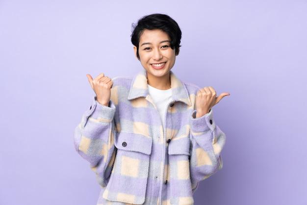 Jovem vietnamita com cabelo curto ao longo da parede com polegares para cima gesto e sorrindo