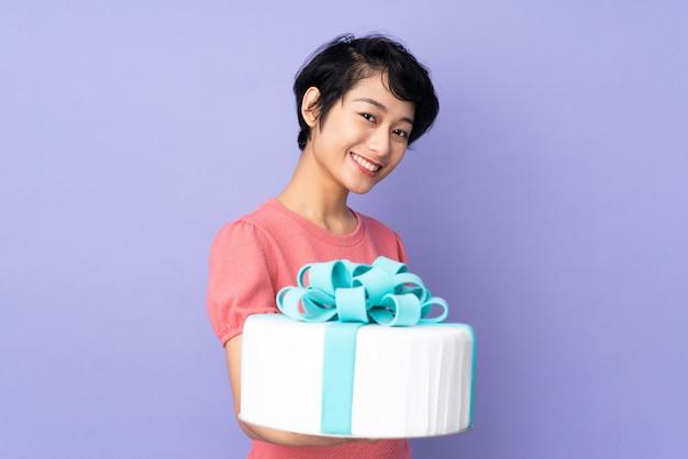 Jovem vietnamita com cabelo curto, segurando um bolo grande sobre parede roxa com expressão feliz