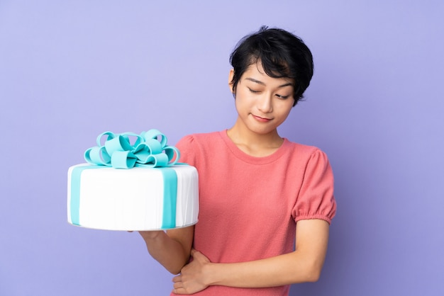 Jovem vietnamita com cabelo curto, segurando um bolo grande sobre parede roxa com expressão triste