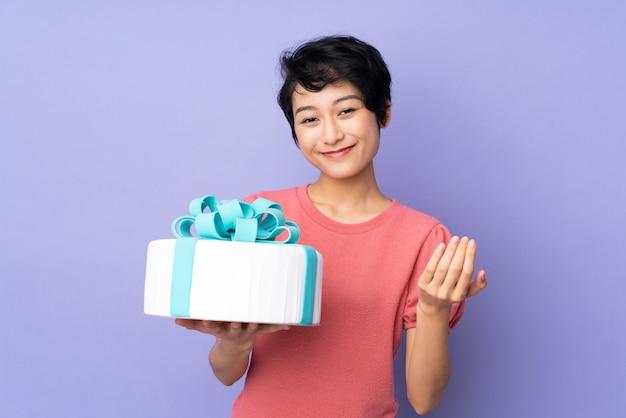 Jovem vietnamita com cabelo curto, segurando um bolo grande sobre parede roxa, convidando para vir com a mão