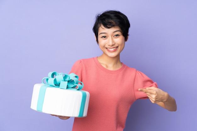 Jovem vietnamita com cabelo curto, segurando um bolo grande sobre parede roxa e apontando-o