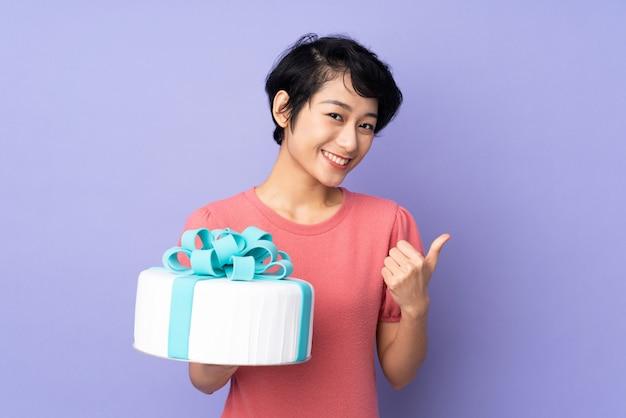 Jovem vietnamita com cabelo curto, segurando um bolo grande sobre parede roxa isolada com polegares para cima, porque algo de bom aconteceu