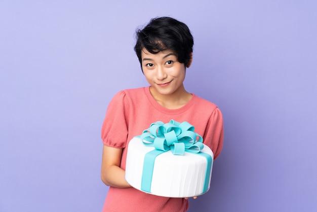 Jovem vietnamita com cabelo curto, segurando um bolo grande sobre parede roxa