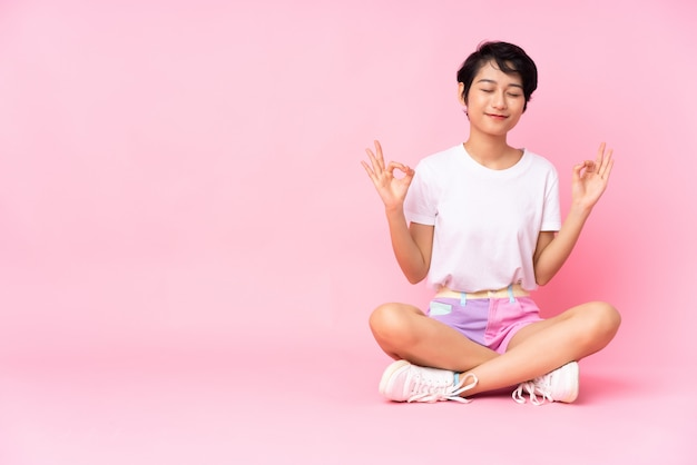 Jovem vietnamita com cabelo curto, sentada no chão sobre parede rosa em pose zen