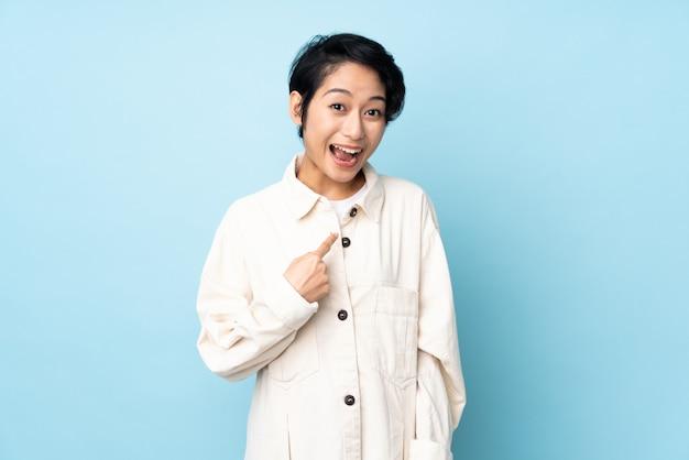 Jovem vietnamita com cabelo curto sobre parede isolada com expressão facial de surpresa