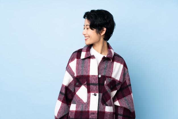 Jovem vietnamita com cabelo curto sobre parede isolada, olhando de lado