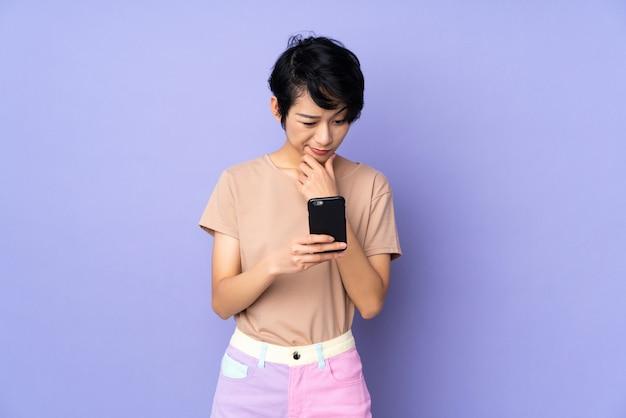 Jovem vietnamita com cabelo curto sobre parede roxa, pensando e enviando uma mensagem