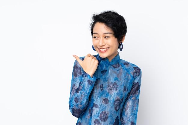 Jovem vietnamita com cabelo curto, vestindo um vestido tradicional sobre branco isolado, apontando para o lado para apresentar um produto