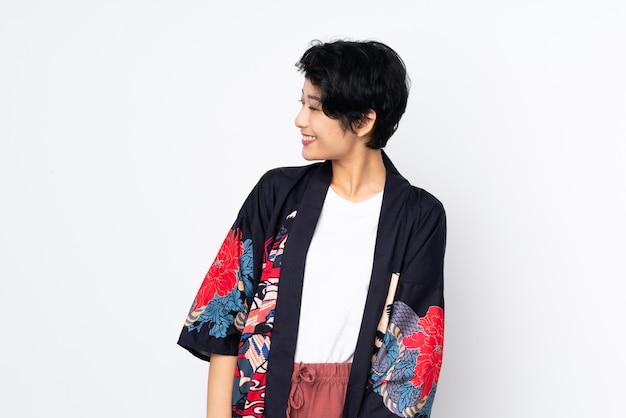 Jovem vietnamita com cabelo curto, vestindo um vestido tradicional sobre branco isolado, olhando de lado