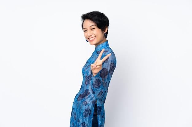 Jovem vietnamita com cabelo curto, vestindo um vestido tradicional sobre branco isolado, sorrindo e mostrando sinal de vitória