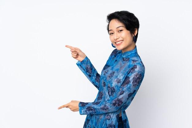 Jovem vietnamita com cabelo curto, vestindo um vestido tradicional sobre dedo apontador branco isolado para o lado e apresentar um produto