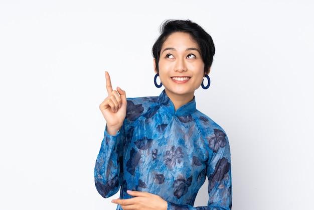Jovem vietnamita com cabelo curto, vestindo um vestido tradicional sobre parede branca isolada, apontando uma ótima idéia