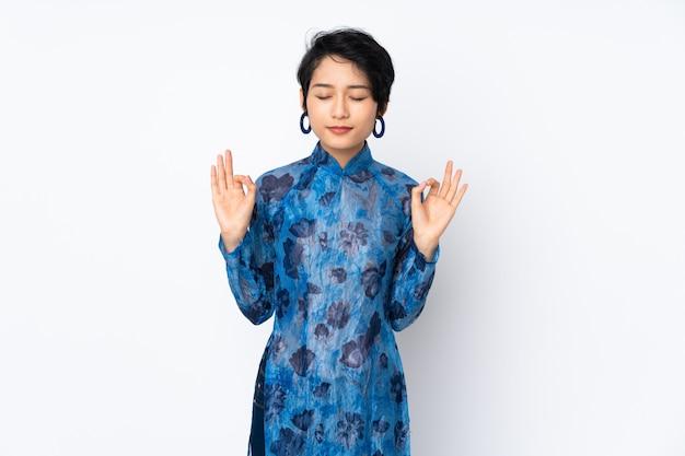 Jovem vietnamita com cabelo curto, vestindo um vestido tradicional sobre parede branca isolada em pose de zen
