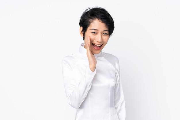 Jovem vietnamita com cabelo curto, vestindo um vestido tradicional sobre parede branca isolada, gritando com a boca aberta