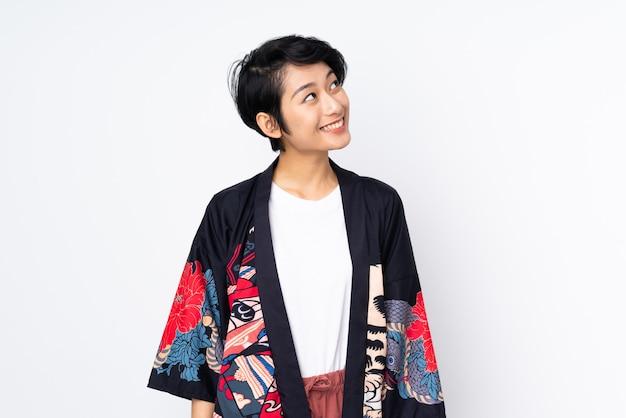 Jovem vietnamita com cabelo curto, vestindo um vestido tradicional sobre parede branca isolada, olhando para cima enquanto sorrindo