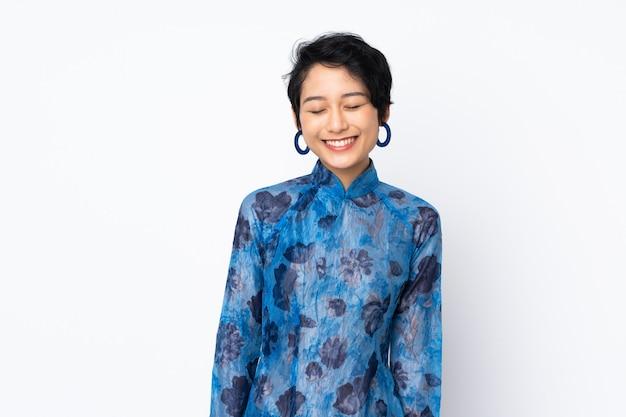 Jovem vietnamita com cabelo curto, vestindo um vestido tradicional sobre parede branca isolada