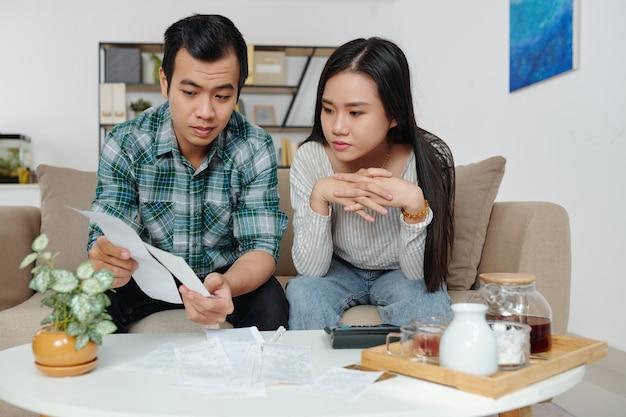 Jovem vietnamita mostrando contas para a namorada quando ela está discutindo e gerenciando despesas pessoais e contas de serviços públicos