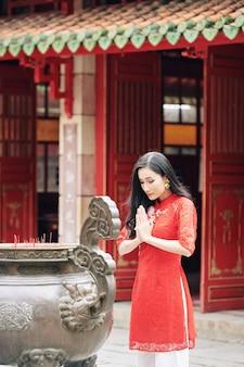 Jovem vietnamita muito calma com vestido vermelho rezando em uma antiga urna de bronze com incensos no templo budista