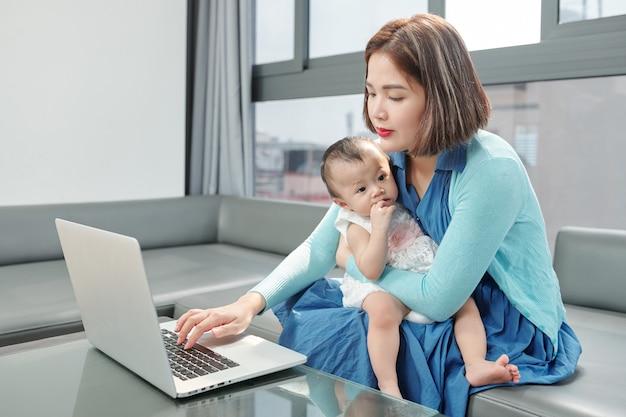 Jovem vietnamita sentada com a filha no colo respondendo a e-mails de clientes