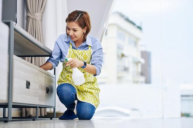 Jovem vietnamita sorridente, limpando a poeira de superfícies de móveis em seu apartamento