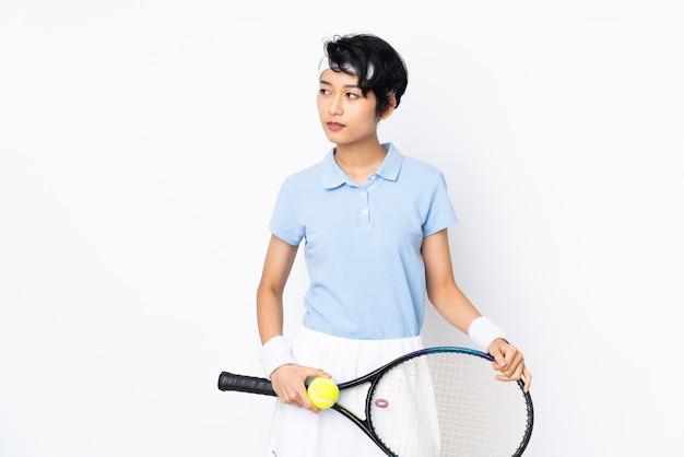 Jovem vietnamita tenista mulher isolada parede branca jogando tênis