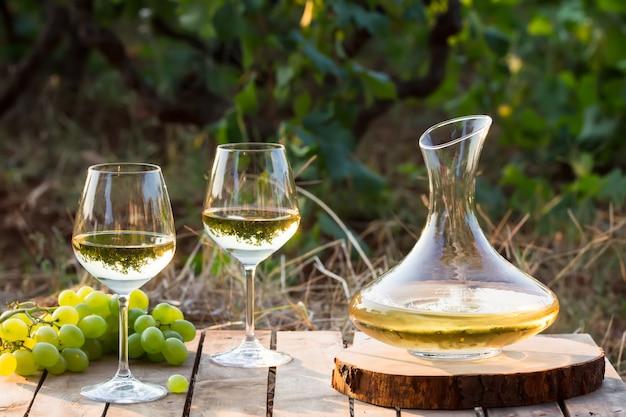Jovem vinho branco na natureza, decanter e uvas brancas