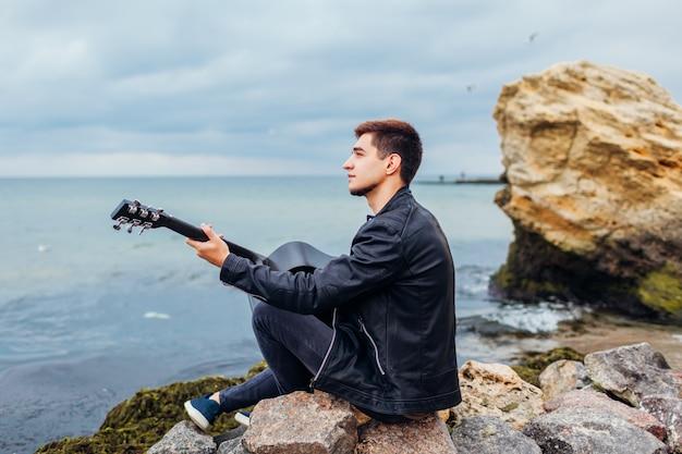 Jovem, violão, tocando, praia, cercado, pedras, chuvoso, dia
