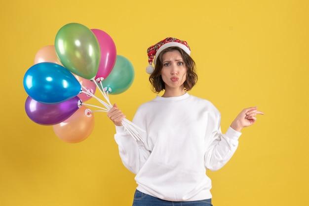 Jovem, vista de frente, segurando balões coloridos em amarelo