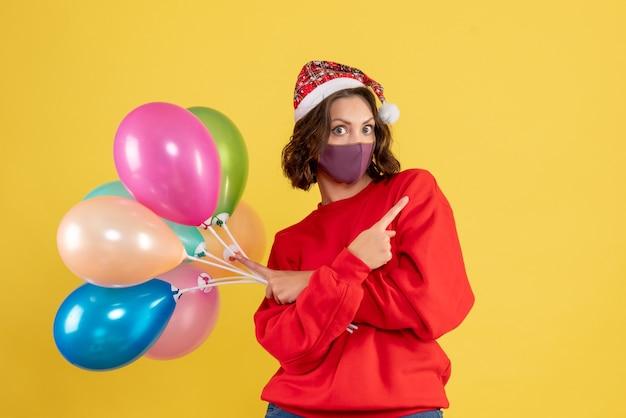 Jovem, vista de frente, segurando balões em amarelo