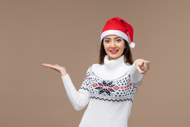 Jovem, vista frontal, com expressão sorridente em fundo marrom, emoção de férias natal
