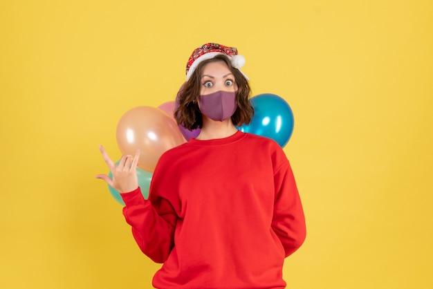 Jovem, vista frontal, escondendo balões em máscara estéril em amarelo