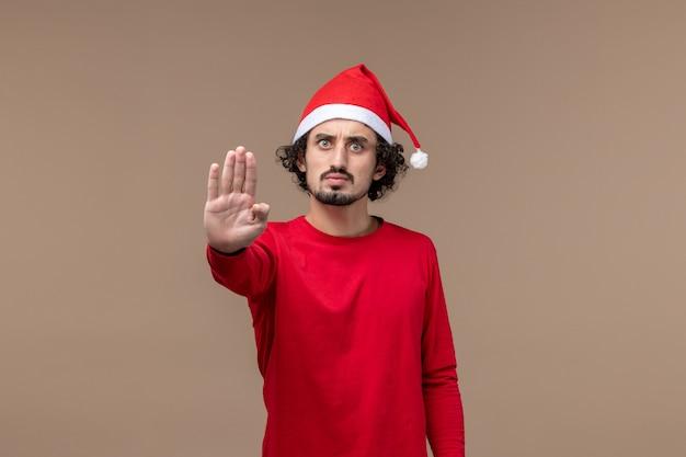 Jovem, vista frontal, pedindo para parar em um fundo marrom, férias emocionantes de natal