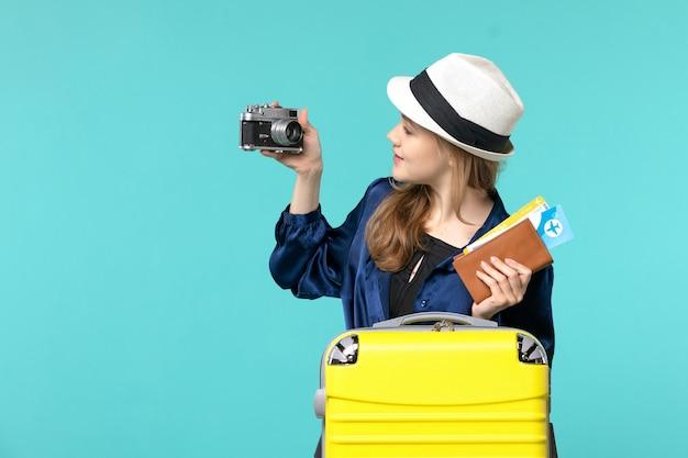 Jovem, vista frontal, segurando a câmera e os ingressos no fundo azul, mulher, viagem, mar, viagem, avião, viagem