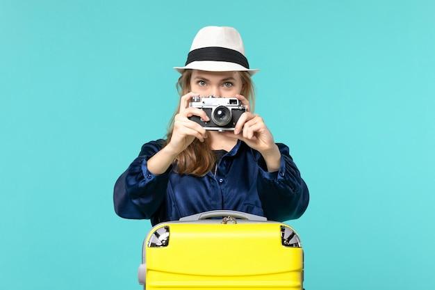 Jovem, vista frontal, segurando a câmera e tirando uma foto no fundo azul, mulher, viagem, mar, viajando, avião de viagem