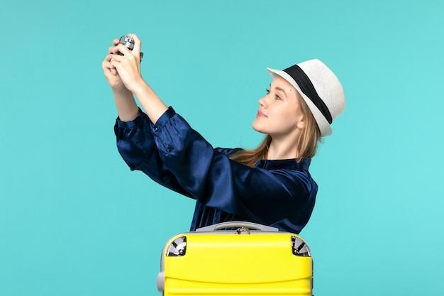 Jovem, vista frontal, segurando a câmera na mesa azul, mulher, viagem, mar, viajando, avião, viagem