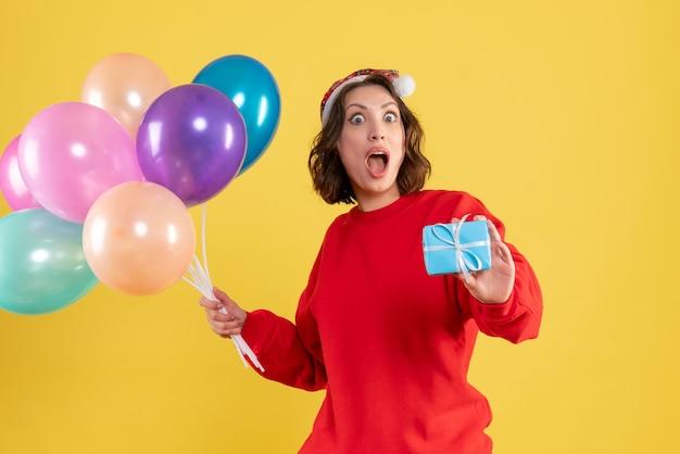 Jovem, vista frontal, segurando balões e presentinho amarelo, natal, natal, ano novo, emoção, cor mulher